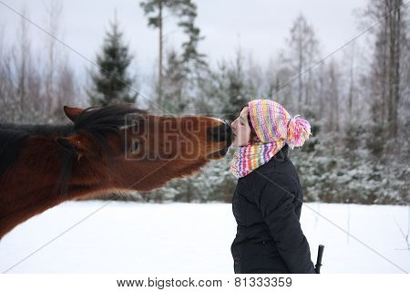 Beautiful Teenager Girl Playfully Kissing Brown Horse In Winter