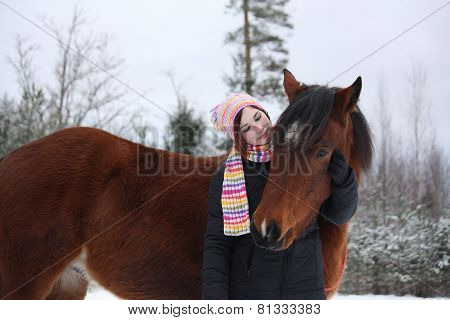 Beautiful Teenager Girl Hugging Brown Horse In Winter