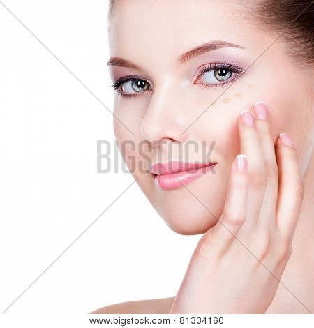 Beautiful face of young woman with cosmetic foundation on a skin over white background. Beauty treatment concept.