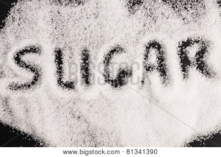 The Word Sugar Written Into A Pile Of White Granulated Sugar