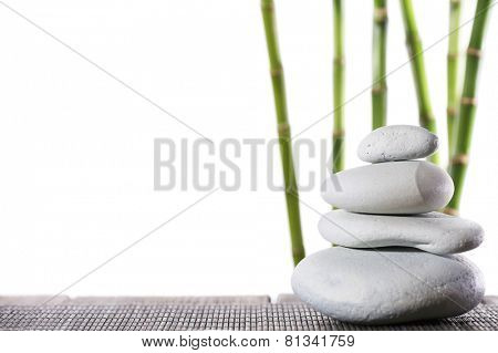 Still life of spa stones on bamboo mat surface with bamboo sticks isolated on white