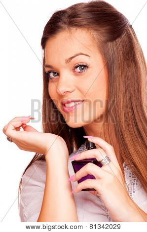Young brunette spraying perfume on her hand and looking at camera, isolated on white