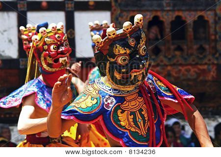 Dancers with colorful mask dance at a yearly festival called tsechu in Bhutan