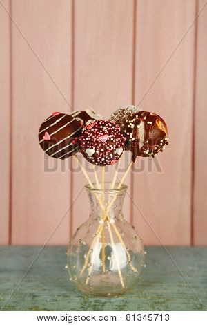 Tasty cake pops on wooden background