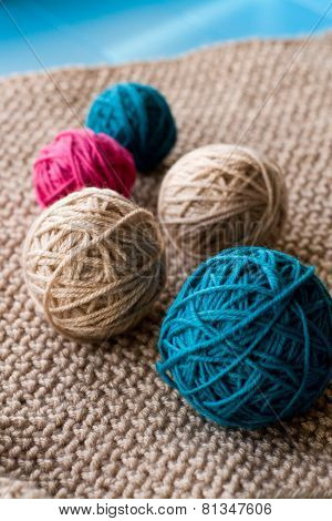 Bright Balls Of Yarn Lying On Beige Knitted Plaid
