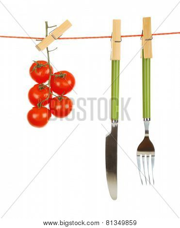 Fork, knife and ripe red tomatoes hanging from clothesline isolated on white background