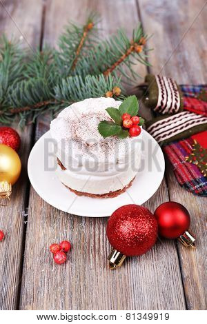 Delicious cake on saucer with holly and berry on Christmas decoration and wooden background