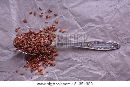 Red rice in spoon on paper background