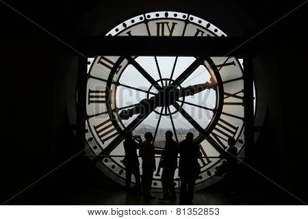 PARIS, FRANCE - JANUARY 8, 2013: Visitors observe a panoramic view thought the glass clock in the Musee d Orsay in Paris, France.