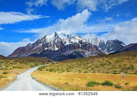 Windy day in early autumn in Patagonia. National Park Torres del Paine. Dirt road goes into the distance