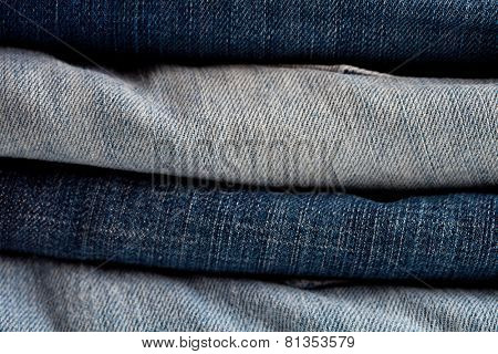 stack of blue and grey jeans as a background or texture