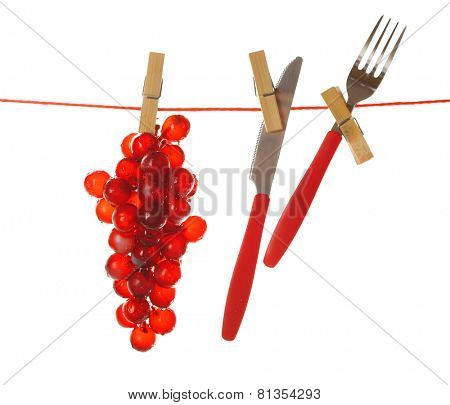 Fork, knife and grape hanging from clothesline isolated on white background