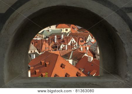 Tiled roofs seen through the wall of the castle garden in Cesky Krumlov, South Bohemia, Czech Republic.