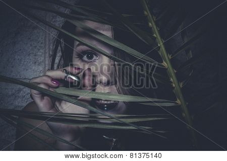 Sensual young girl hidden behind the branches of a tree