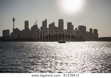 Sydney distant CBD silhouette of skyscrapers and towers at sunset against the sun summer time heat in the city, Australia .