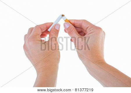 Close up of a woman breaking cigarette on white background