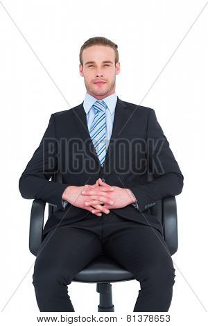 Stern businessman sitting on an office chair on white background