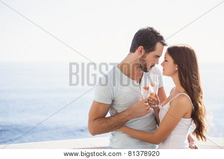 Cute couple toasting with champagne on their balcony