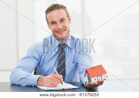 Businessman taking notes and showing miniature house in his office