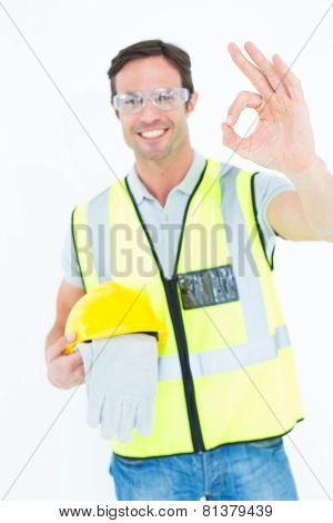 Portrait of carpenter holding gloves and hardhat while gesturing OK sign against while background