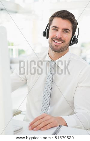 Happy businessman with headset interacting in his office