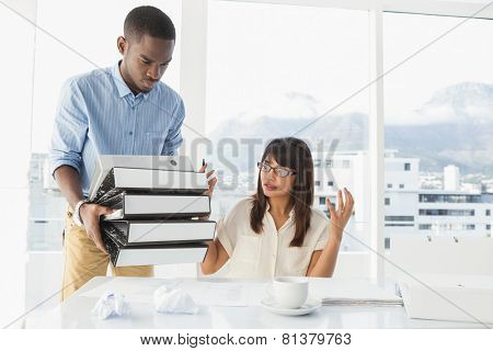 Man giving pile of files to his exasperated colleague in the office