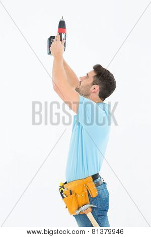 Side view of repairman using hand drill against white background