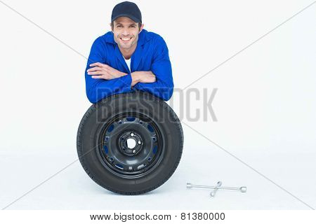 Portrait of handsome mechanic leaning on tire over white background