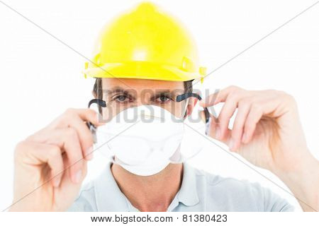 Close-up portrait of worker wearing protective glasses over white background