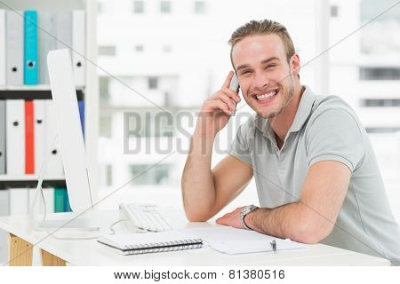 Smiling businessman making a call in his office