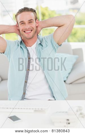 Smiling businessman relaxing with hands behind head in his office