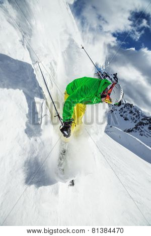 Skier skiing downhill in high mountains during sunny day.