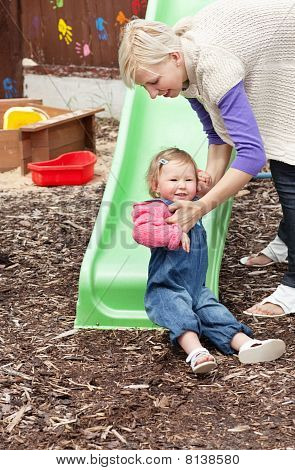Little Girl And Her Blond Mother Having Fun With A Chute