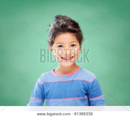 education, school and children concept - little student girl over green chalk board background