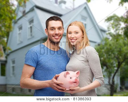 love, people, real estate, home and family concept - smiling couple holding piggy bank over house background