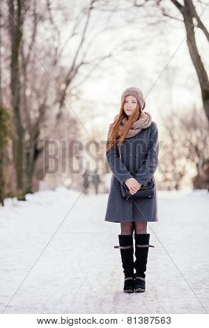 Winter full length portrait of a cute redhead lady