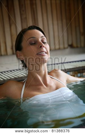 Beautiful woman relaxing in spa swimming-pool