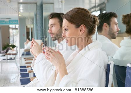 Portrait of couple in bathrobe sitting in relaxation room