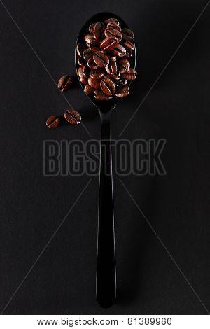 Roasted coffee beans on black spoon