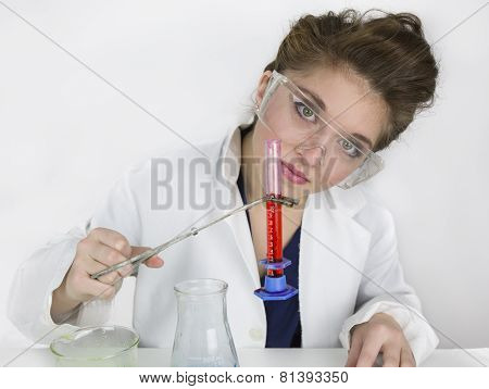 Teenage girl wearing goggles doing science experiment