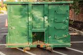 pic of dumpster  - Green unloaded construction dumpster on parking lot area in front of the building - JPG
