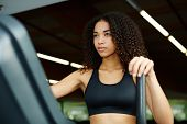 foto of time machine  - Beautiful afro american woman with curly hair exercising in gym on a step simulator machine beautiful and healthy woman enjoying time at gym - JPG