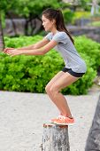 stock photo of work bench  - Fitness woman athlete bench jump squat jumping outside in nature landscape - JPG