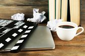 stock photo of clapper board  - Movie clapper with laptop and cup of coffee on wooden background - JPG