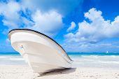 stock photo of atlantic ocean beach  - White pleasure motor boat lays on sandy beach - JPG