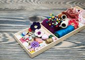 stock photo of handicrafts  - thread and material for handicrafts in box on a wooden background - JPG