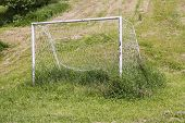 picture of neglect  - Neglected soccer goall on an uncut grass - JPG