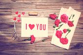 stock photo of carnation  - I Love You theme with scissors twine and carnation flowers on grungy background - JPG