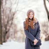 foto of stroll  - Winter portrait of a cute redhead lady in grey coat and scarf strolling in the park - JPG