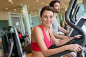 image of cardio  - Woman in fitness club using cardio equipment - JPG